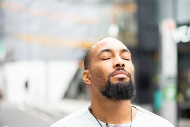 A moment of serenity A handsome man standing outside with his eyes closed, enjoying a moment of peace. mental wellbeing stock pictures, royalty-free photos & images