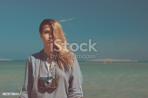 photographer woman on the beach looking at camera and feeling the wind in her hair, lifestyle and relaxing moment near the sea side.
