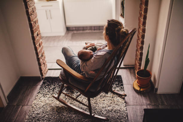 mommy and baby in a rocking chair - tranquil scene stock pictures, royalty-free photos & images