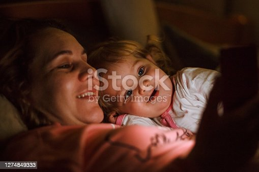Shot of smiling mother cuddling her cute baby girl while lying in bed in the evening and enjoying watching fun cartoons on smart phone she is holding.