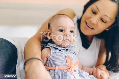 Gorgeous 3 month old little baby girl on a bed in a domestic home in a casual photograph with her mother. Mother is of Peruvian descent. They are happy in their home, new baby, light and bright, discovering the world