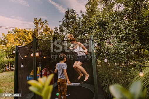 Photo of mother and son jumping together on a trampoline