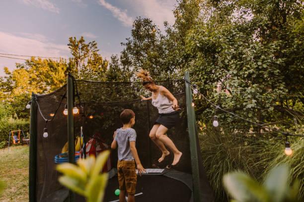 Mama und Sohn springen zusammen auf einem Trampolin – Foto