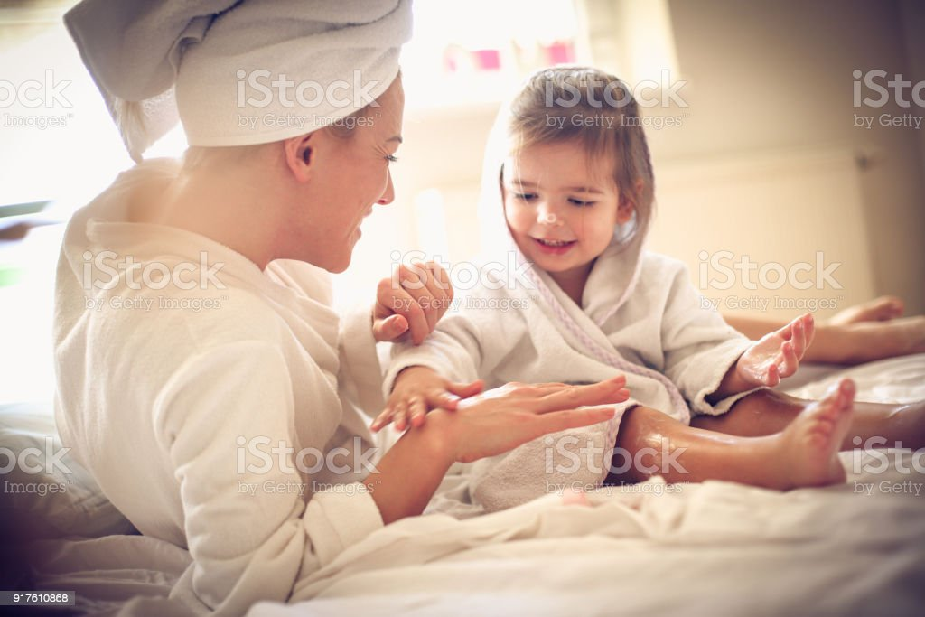 Mommy can I apply body lotion on your hand. Little girl. stock photo