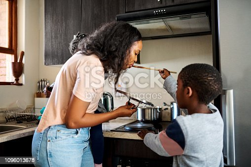 Shot of a little boy giving his mother a taste of the food he's preparing at home