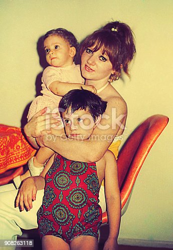Vintage  photo from the seventies featuring a mother and hugging her daughter and son