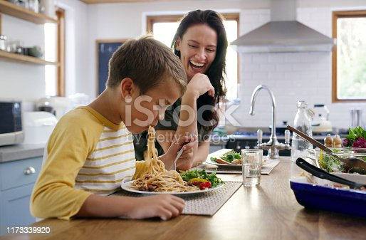 Cropped shot of an affectionate young boy going in on his spaghetti while his mother laughs in the background