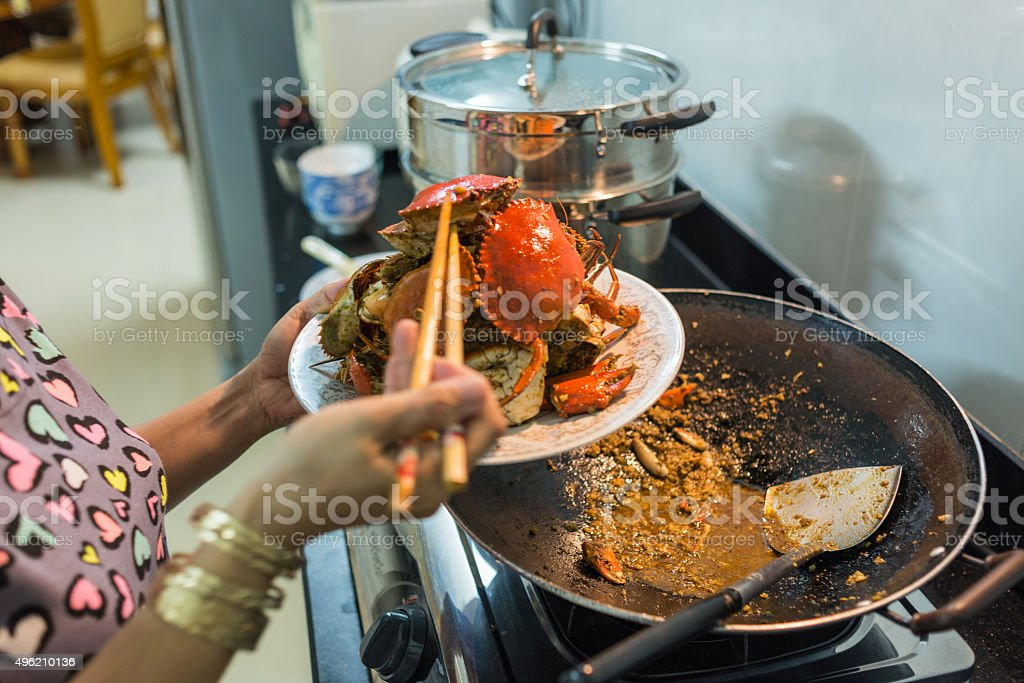 Mommy using chopsticks to pick crab into the dish stock photo