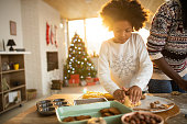 Adorable girl with Afro hair helping mom in the kitchen to make cookies