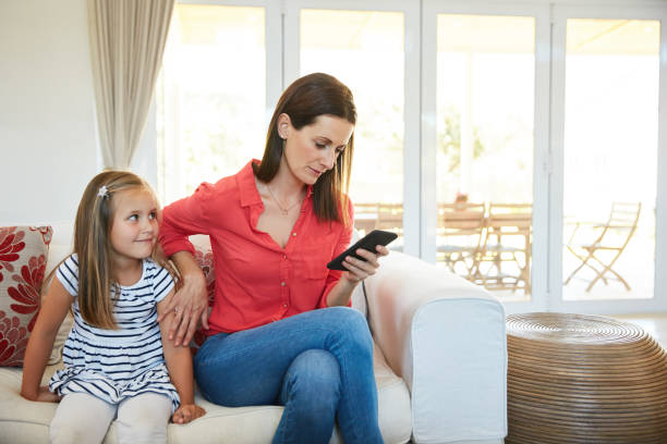Mommy's busy right now Shot of a mother using a cellphone and her young daughter sitting together in the living room at home ignoring stock pictures, royalty-free photos & images