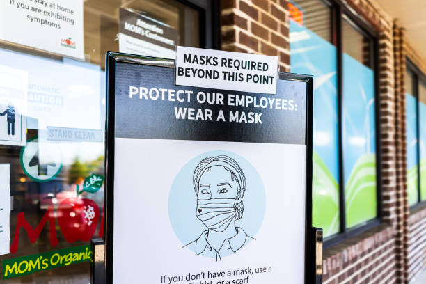 Mom's Organic Market store in Virginia with sign to wear face mask covering beyond this point corona virus stock photo