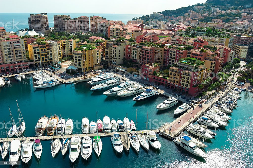 Monaco harbor with yachts and speed boats Scenic view of boats and luxury yachts moored in Fontvielle harbour and marina of Monte Carlo, Monaco, South of France. Aerial View Stock Photo