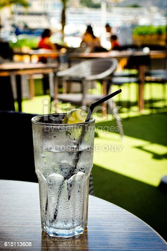 Monte Carlo, Monaco - July 30, 2015: A cold lemonade on a table with an out of focus background of a harbour side restaurant.