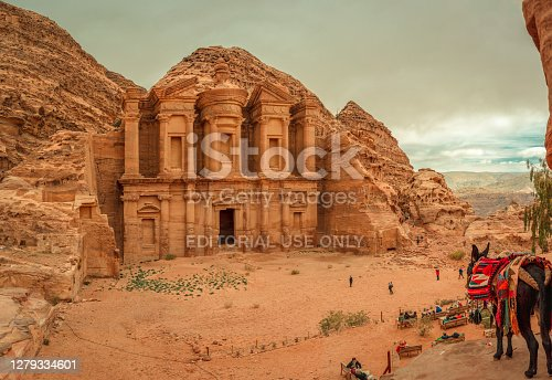Petra, Jordan - January 13 2020: Tourists look tiny in front of the vast Monastery (El Deir), the largest monument on the archaeological site, built by the Nabataeans, on a cloudy day.