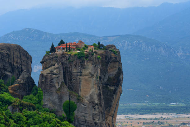 Monastery Holy Trinity, Meteora, Greece. UNESCO world heritage Site. Epic spring landscape with temple at the edge of cliff at dramatic sky background. stock photo
