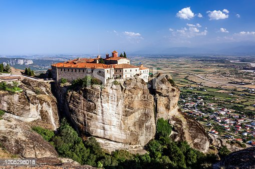 Monastery Meteora Greece. Stunning summer panoramic landscape. View at mountains and green forest against epic blue sky with clouds. UNESCO heritage list object.