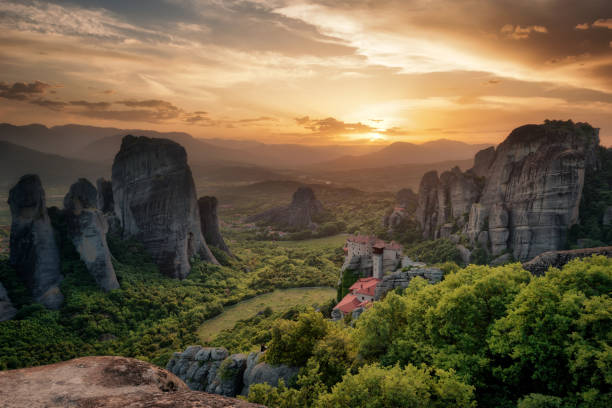 Monastery Meteora Greece. Stunning spring panoramic landscape at sunset. View at mountains and green forest against epic sky with clouds. UNESCO heritage list object. The Holly Monastery of Rousanou. stock photo