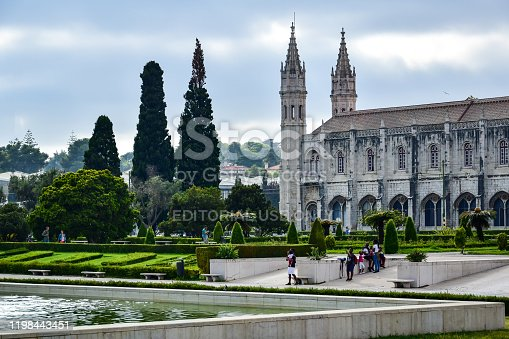 Lisbon, Portugal - 07.16.2019: Monastery of the Hieronymites (Mosteiro dos Jerónimos), a park near the building, green trees and bushes, tourists walk, in the summer afternoon.