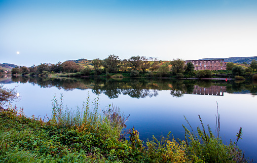 Monastery ruin Stuben and the village Bremm at the Moselle riverside in the evening Germany