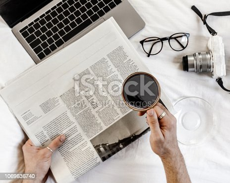 Man drinking his early morning coffee and reading news paper on this bed
