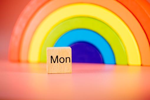 Monday wooden block on rainbow background