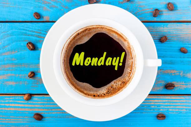 montag wort am morgenkaffee tasse auf blauem hintergrund aus holz. anfang der woche - glückliche montagszitate stock-fotos und bilder