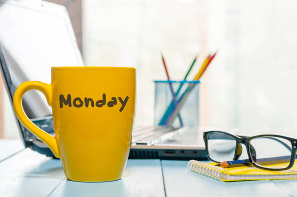 monday written on yellow coffee or tea cup at wooden boards table, workplace, office sunlight morning background - monday motivation stock photos and pictures