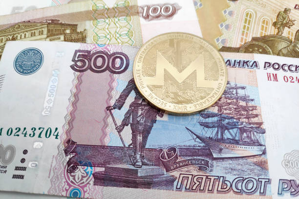 Monero coin on top of a stack of Russian Rubles stock photo