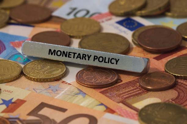 monetary policy - the word was printed on a metal bar. the metal bar was placed on several banknotes series of words printed on a metal bar. the metal bar was placed on several banknotes monetary policy stock pictures, royalty-free photos & images