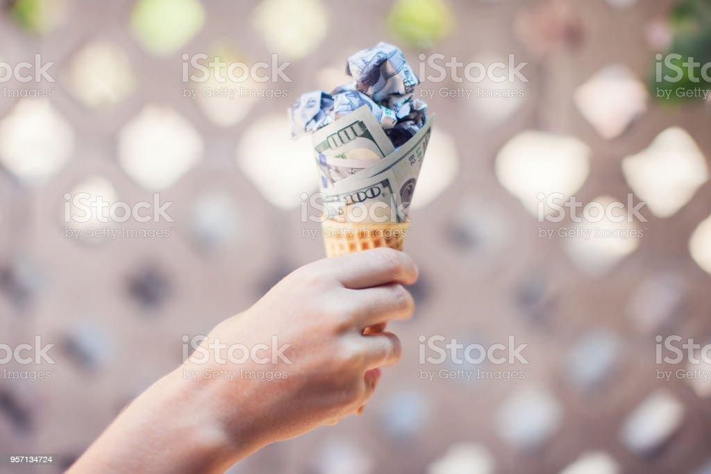 Monetary wafers. dollar bills rolled in ice cream cone stock photo