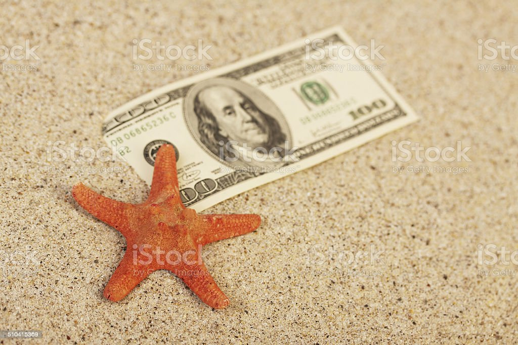 Money american hundred dollar bills in sand and sea aster stock photo
