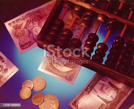 istock Money and abacus - ancient calculating tools that are still used today 1209190934