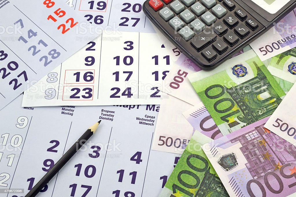 Money and calculator on  month calendar stock photo