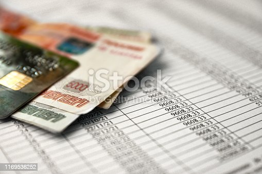 Money and credit card on a loan agreement paper form with loan repayment schedule.
