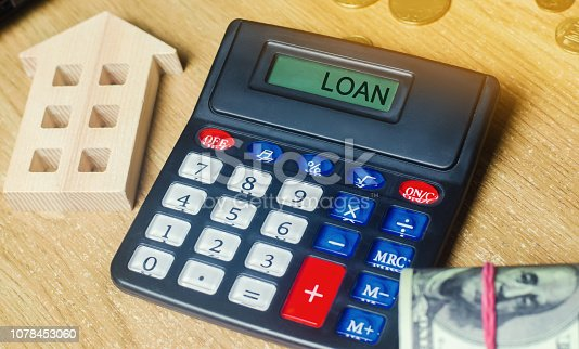 Money and houses on the table and a calculator with the word Loan. The concept of buying property in debt. Analysis of costs and revenues. Apartment purchase. Selling a house. Credit and mortgage.
