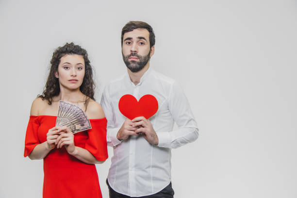 money and love. dollar hands. a man holds a red heart in his arms a wife holds the money. valentine's day white background. - holiday and invoice family foto e immagini stock
