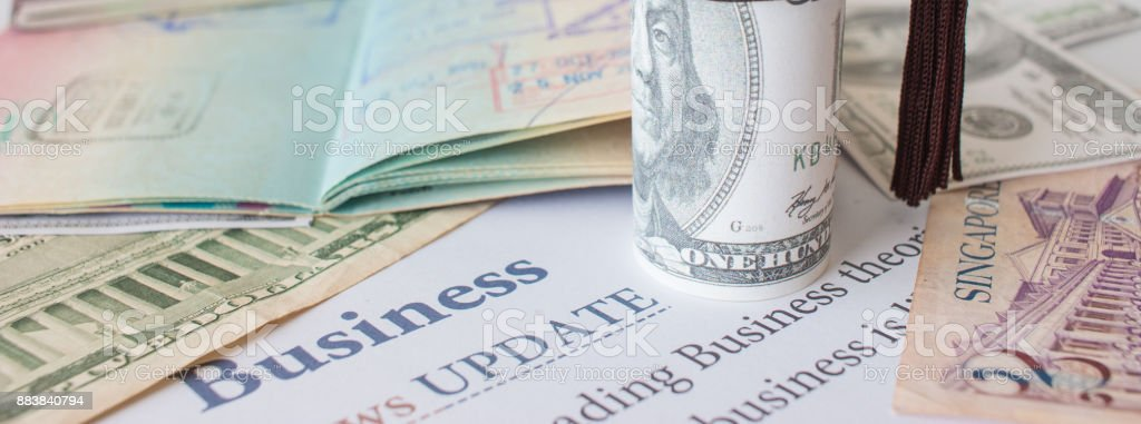 Money and passport with on letter book, Business News update, Concept of graduate education MBA abroad in university, requires a lot foreign currency Dollars to bring success in famous institution stock photo