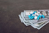 istock Money and pills. Various medicines and pills on background of USA dollars banknotes. Expensive medicine. Medical insurance. Drug addiction. 1135349373
