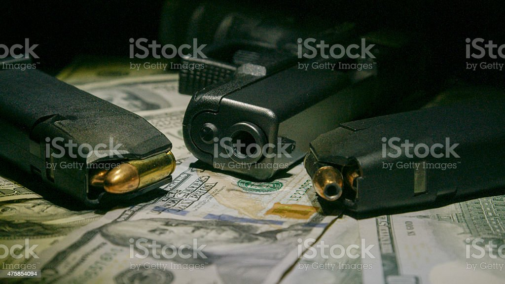 Money and Pistol on One Hundred Dollar Bills stock photo