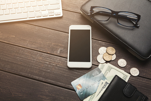 istock Money and smartphone on wooden table 962178938