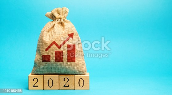 1170746979 istock photo Money bag and up arrow with wooden blocks 2020. Business forecasting. Growth and development of business and economy. Planning. Strategy and management. Targets and goals. Financial plan 1210180456