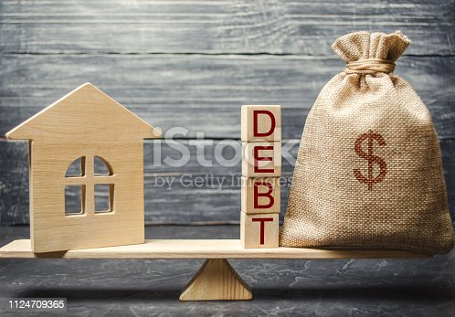 istock Money bag and wooden blocks with the word Debt and a miniature house on the scales. Payment of debt for real estate. Pay off the mortgage loan. Risks of buying a house. Buying an apartment on credit. 1124709365