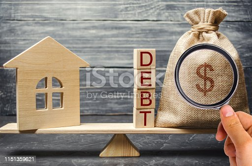 istock Money bag and wooden blocks with the word Debt and a miniature house on the scales. Payment of debt for real estate. Pay off the mortgage loan. Risks of buying a house. Buying an apartment on credit. 1151359621