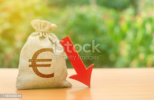 istock Money bag with Euro symbol and red arrow down. Reduced profits and liquidity of investments. Reduced tax revenues, economic difficulties, departure of capital, investors. Falling wages and welfare 1162403249