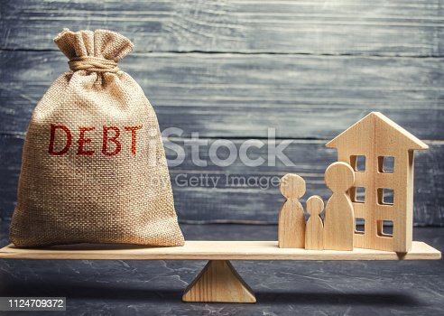 istock Money bag with the word Debt and a miniature house with a family on the scales. Payment of debt for real estate. Pay off the mortgage loan. Risks of buying a house. Buying an apartment on credit 1124709372