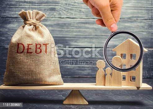 istock Money bag with the word Debt and a miniature house with a family on the scales. Payment of debt for real estate. Pay off the mortgage loan. Risks of buying a house. Buying an apartment on credit 1151359651
