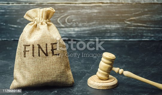 1024130248 istock photo Money bag with the word Fine and the judge's hammer. Penalty as a punishment for a crime and offense. Financial punishment. Violations of traffic laws. Fraud. Fines can also be used as a form of tax 1129689180