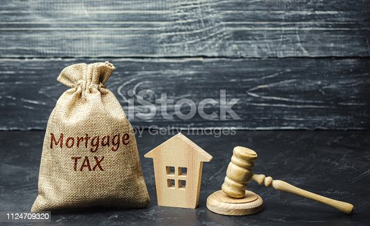 1024130248 istock photo Money bag with the word Mortgage tax, judge's hammer and wooden house. Mortgage credit lending. Tax refund when buying an apartment in the mortgage. Court. Law. Gavel. Interest rates. Real estate 1124709320