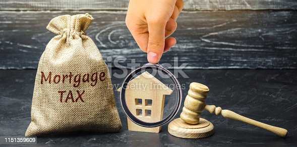 1024130248 istock photo Money bag with the word Mortgage tax, judge's hammer and wooden house. Mortgage credit lending. Tax refund when buying an apartment in the mortgage. Court. Law. Gavel. Interest rates. Real estate 1151359609