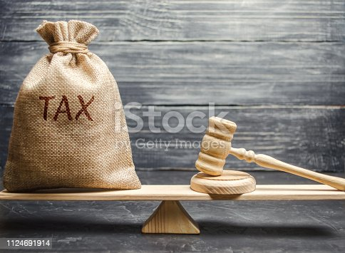 1024130248 istock photo Money bag with the word Tax and hammer judge on the scales. The concept of paying taxes and debt repayment. Register of taxpayers for property. Property taxes and mortgages. Gavel 1124691914